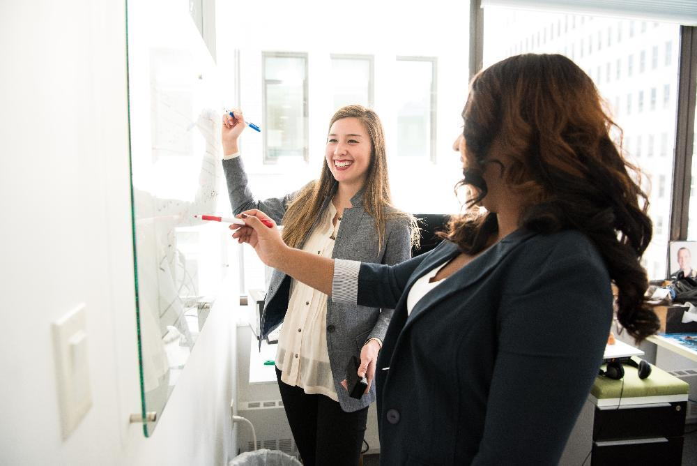 Women smiling and drawing on a whiteboard